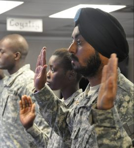 Soldiers stand with right arms raised to take the oath of citizenship.