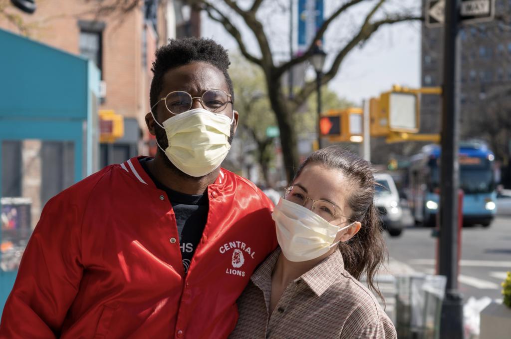 Couple wear face masks on sidewalk.