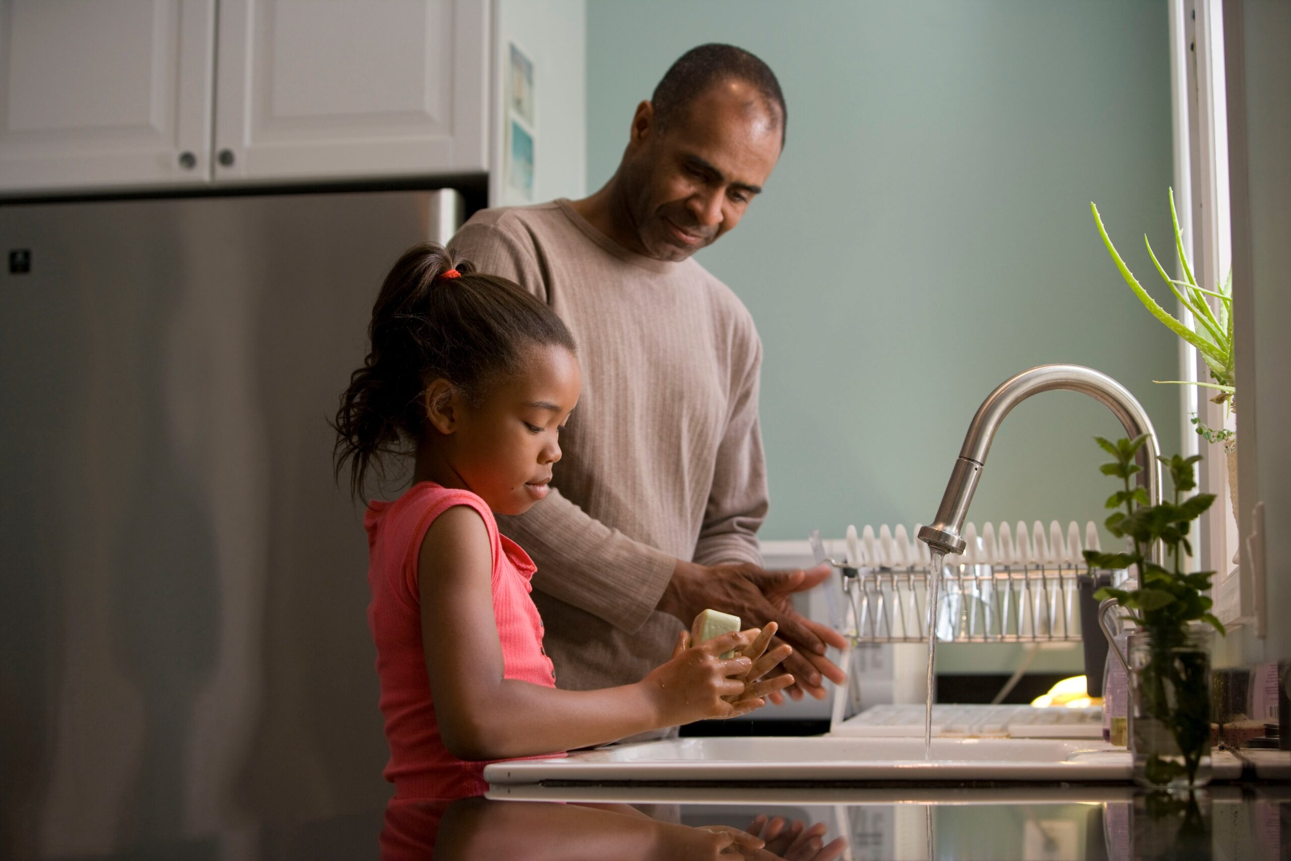 Man and daughter filling pitcher