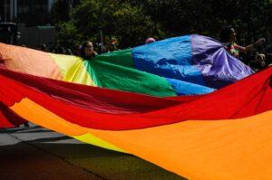 People hold large rainbow flag