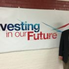Superintendent Ronald Drzewicki stands in front 'Investing For the Future', the May bond proposal