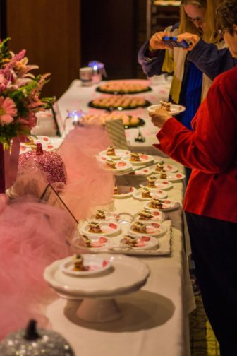 Guests admiring the pink desserts and trying them.