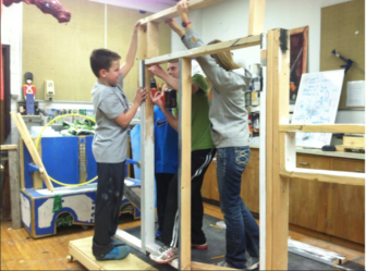 """Set construction crew members Brandon Lee, Braden Stirret, Matthew Kloc and Amelia Arnold. Taken in the scene shop, in preparation for """"The Wind in the Willows."""" Photo Credit: Sarah Willis"""