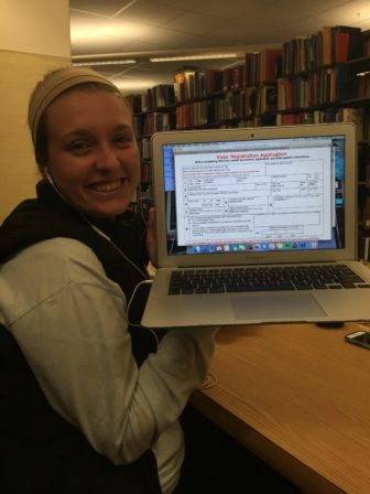 Junior education major Emily Crawford at the MSU library showing off her completed Registration Form