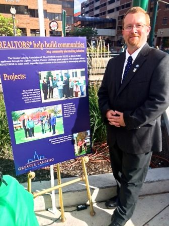 "Matt Robertson standing next to his poster reading, ""Realtors help build communities."""