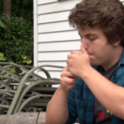 Michigan State student Wes Walters smokes a cigarette at his off-campus home