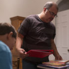 Stay-at-Home dad, Domingo Quintanilla organizes lesson plans for the day. Quintanilla homeschool his two youngest boys. His older son Jorryn Platte, 12, attends a public school in Grand Ledge.