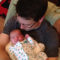 Ryan Pelerin, father of three holds his one-month-old daughter Vivienne. Pelerin took paternity leave for each of his children.