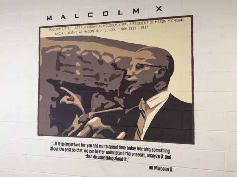 """A mural of Malcolm X displayed in a hallway at Mason High School. The bottom quote reads: """"...It is so important for you and me to spend time today learning something about the past so that we can better understand the present, analyze it and then do something about it."""""""