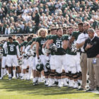 Players from the Michigan State football team stand for the national anthem before a game this past season.