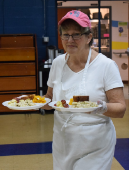 A volunteer at Southside Community Kitchen delivering food to the guests.