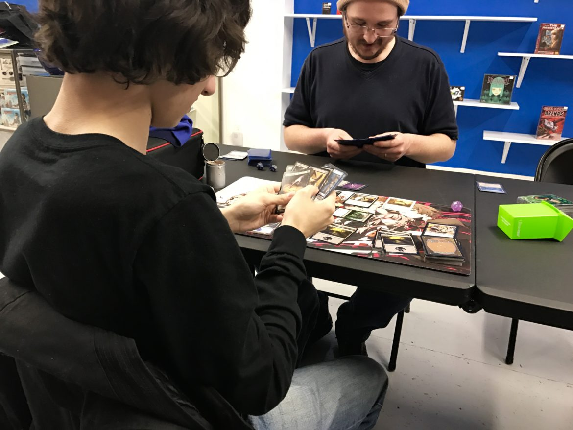 "Justin McVay, owner of Manafold Games, plays Magic the Gathering with a local teen. ""I like that this place is going to be a community center for teens,"" he said."