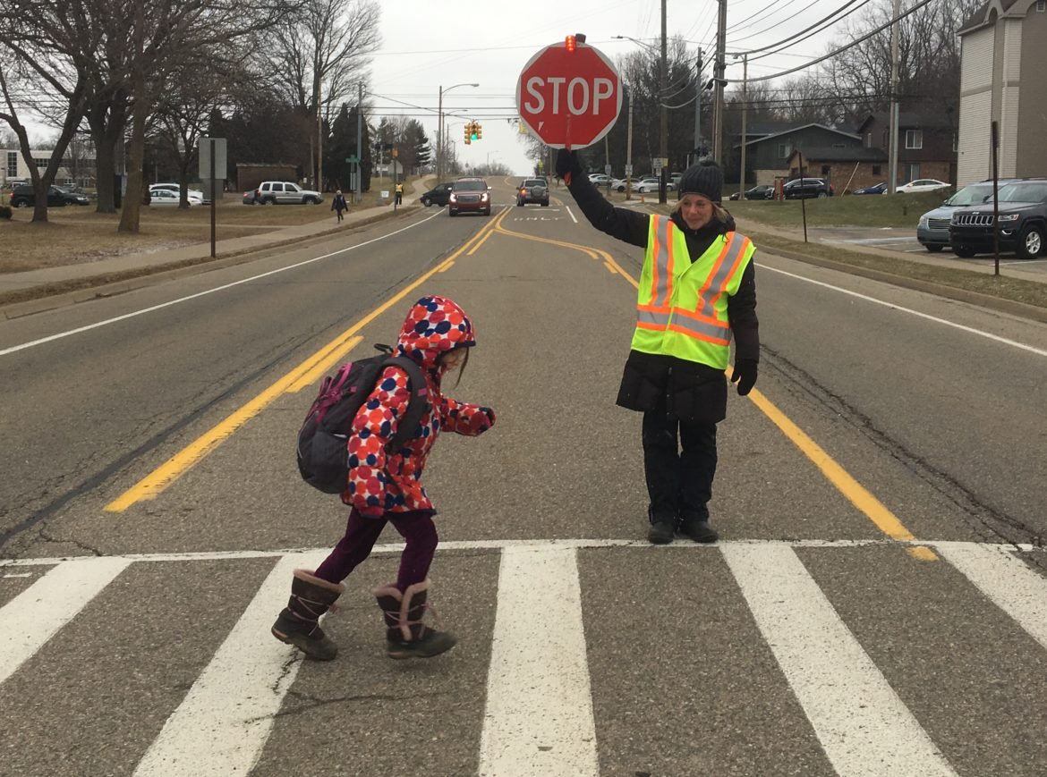 Crossing guard Sarah Murray helps an elementary student cross the street.
