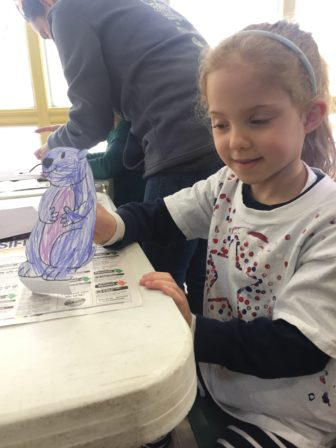 Little girl creating a craft on Groundhogs day at Harris Nature Cetner