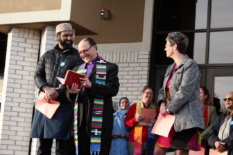 Iman Sohail Chaudhry of the Islamic Center of East Lansing, United Methodist Bishop of the Michigan Area Bishop David Bard and Rabbi Amy Bigman of the Congregation Shaarey Zedek smiling on a platform.