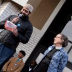 Imam Sohail Chaudhry of the Islamic Center of East Lansing and Parish Associate Alice Townley of the Presbyterian Church of Okemos smiling on a platform.