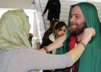 Co-President of the MSU chapter of Project Nur, Erin Wilson ties a hijab for MSU student Elias Zimmer