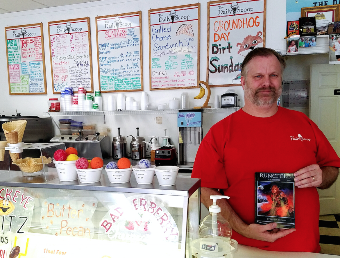 Shawn Sodman holding his book, Runefell Crossroads, in his ice cream shoppe, The Daily Scoop.