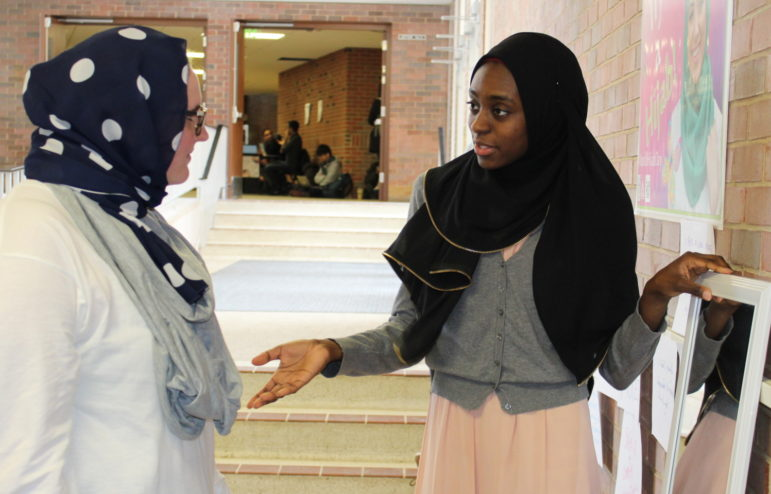 Hauwa Abbas from the Michigan State Muslim Students' Association shows first-time hijab wearer Emily Vos what she looks like.