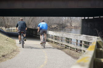 Two bicyclists enjoy a warm March day on the Lansing River Trail. Photo by Lukas Eddy
