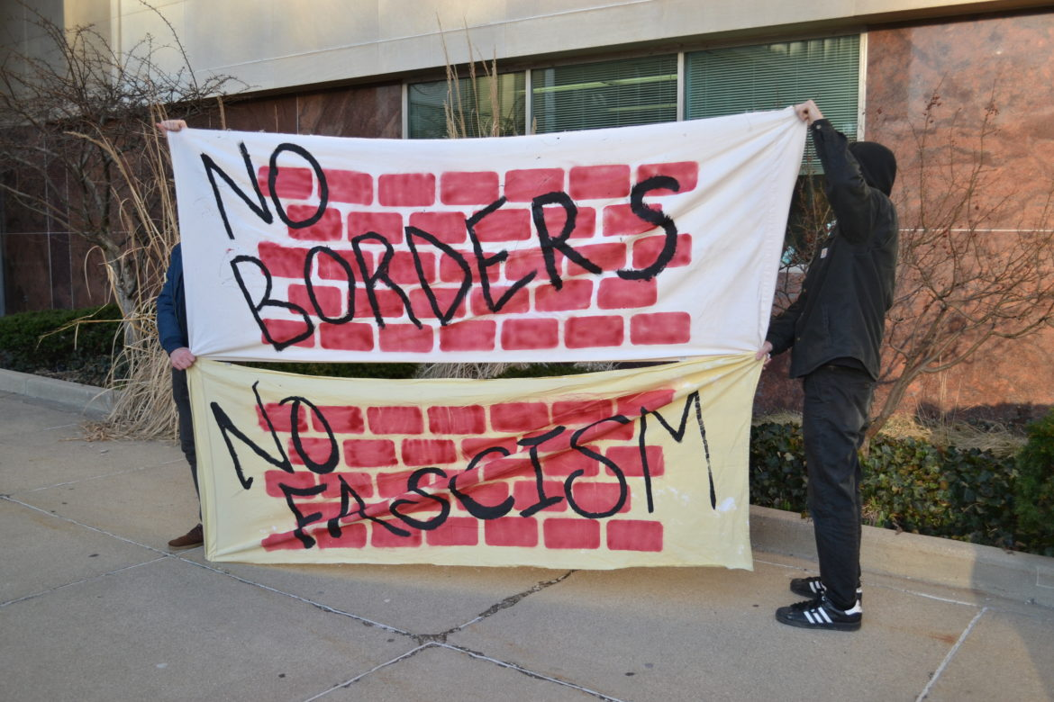 Lansing residents stood outside of the city council meeting on Monday, Feb. 27 with a banner to show support for a sanctuary city resolution.