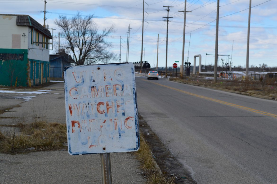 """A rusted sign that used to read, """"Video camera watches parking lot,"""" sits outside an abandoned building in Lansing Township. Photo by Hannah Holliday."""