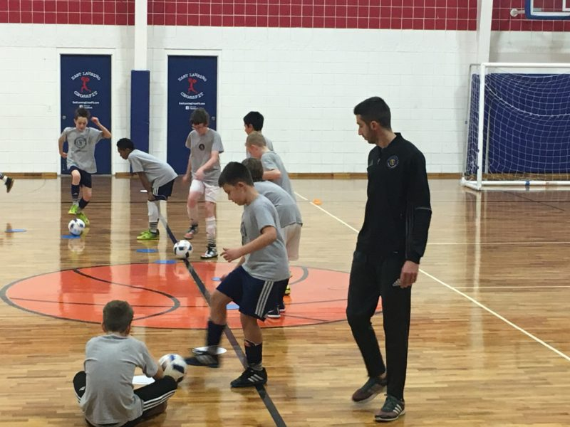Lucas Capalbo watches as his players perform dribbling drills. Photo by Zachary Manning