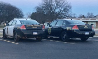 A pair of Lansing Township Police cars sit in the parking lot of the Lansing Township Police Department on Michigan Ave. First responders in Lansing Township can be dispatched to emergencies in surrounding jurisdictions outside the township. Photo by Casey Harrison.