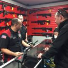 Employee at Not Just Guns discussing a firearm with customers.