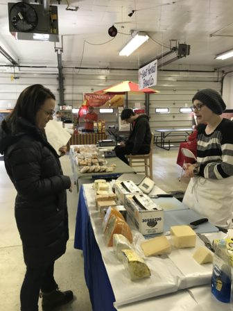 A women scans the cheese stand and converses with the vendor on March 11. Photo by Claire Barkholz.