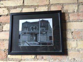Framed picture of the Creole building prior to Robert Busby's purchase. Photo courtesy of Jamie Schriner-Hooper. Photo taken by Alexis Downie.