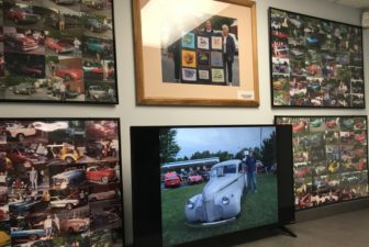 Pictures of cars and their owners that have stopped at Olympic Broil through the years line a wall in the restaurant. Photo by Kaley Fech.