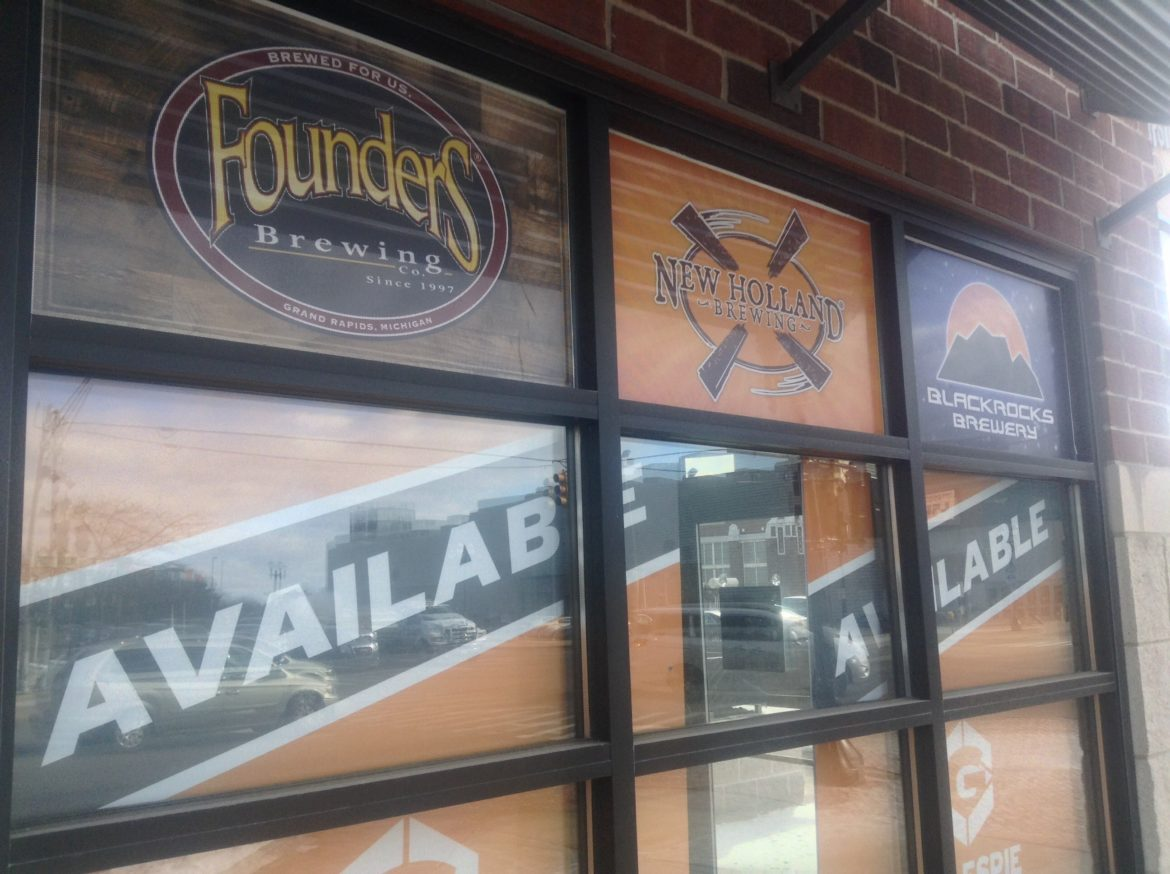 """The former Beer Grotto 500 Michigan Ave. in Lansing shows off the craft beers it once served above """"Available"""" signs in its front windows. Photo by Maxwell Evans"""
