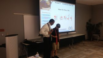 Skills learned at the LPSYLA can be applied to many other aspects of life - even knowing how to tie a tie. Photo courtesy of the Lansing Police Department, Lt. Rodney Anderson and Officer Kasha Osborn.
