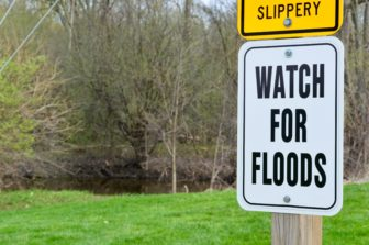A sign warns pedestrians who are using the Lansing River Trail to watch for floods. Photo by Hannah Holliday.