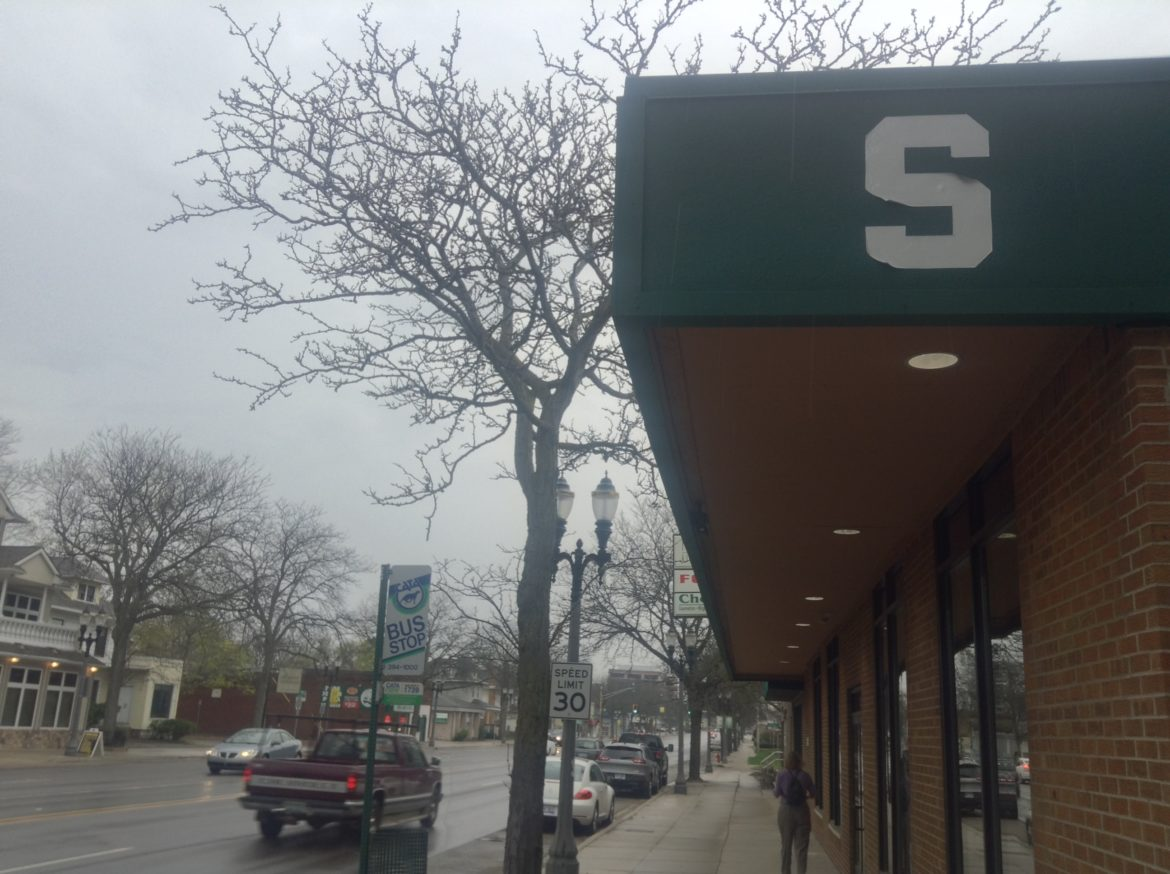 "The Michigan State ""S"" is visible on the awning of the university's Center for Community and Economic Development on Michigan Avenue. The center is one of many outreach programs connecting MSU with its neighbor to the west. Photo by Maxwell Evans"