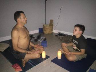 Cerneant with his son, Sage, in the middle of a yoga pose.