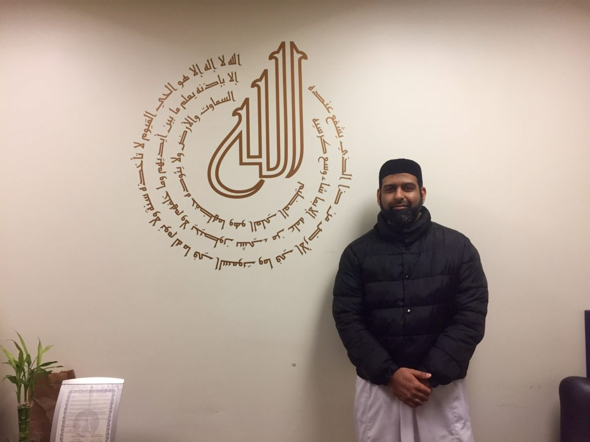 Sohail Chaudhry, standing in front of a verse from the Quran in his office at The Islamic Center of East Lansing Thursday, Mar. 2, 2017.