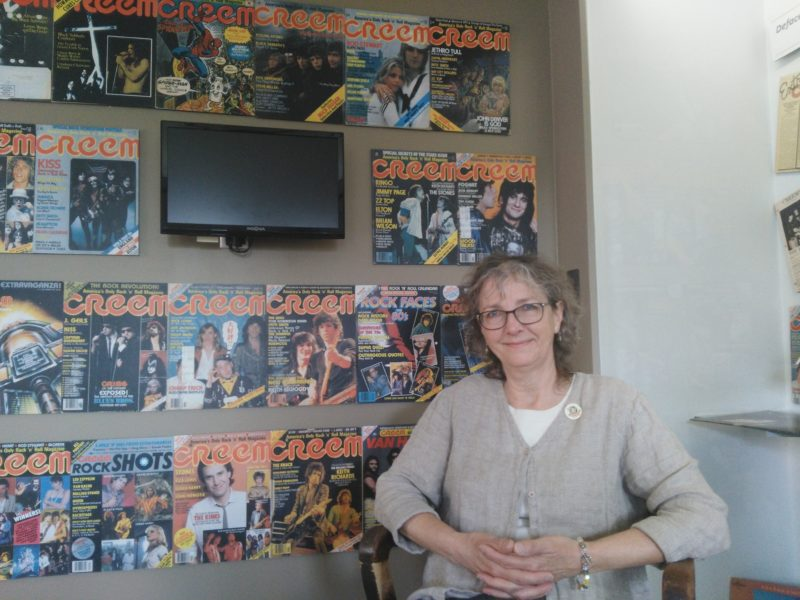 Leslie Pielack, Director of the Birmingham Museum sitting in front of a collection of frontages from CREEM Magazine. Photo by Simone Fenzi.