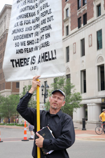 Dan Widmayer holds a poster with his belief during the Michigan Pride March at the Capitol Building area on June 17, 2017.