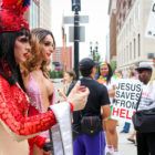 Two paraders are pictured with one of the protestors during the Michigan Pride March at the Capitol Building, East Lansing, Michigan on June 17, 2017.