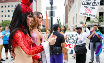 Two paraders are pictured with one of the protestors during the Michigan Pride March at the Capitol Building, East Lansing, Michiganon June 17, 2017.
