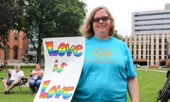 """Former Sheridan resident, now Lansing resident Phoebe Gohs shows the sign """"Love is Love"""" during the Michigan Pride March at the Capitol Building on June 17, 2017."""