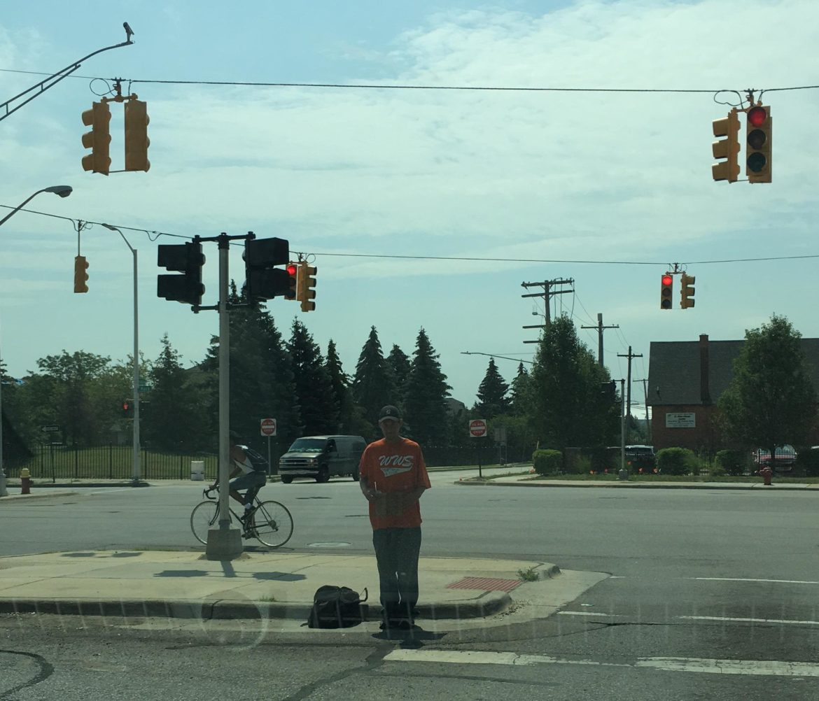 Homeless man standing on street in Detroit asking for money.