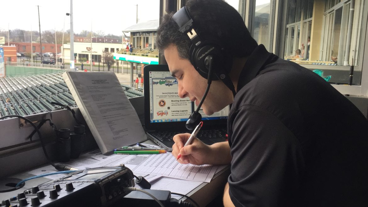 Lansing Lugnuts play-by-play announcer Jesse Goldberg-Strassler comments on a game in the broadcasting booth of Cooley Law School Stadium.