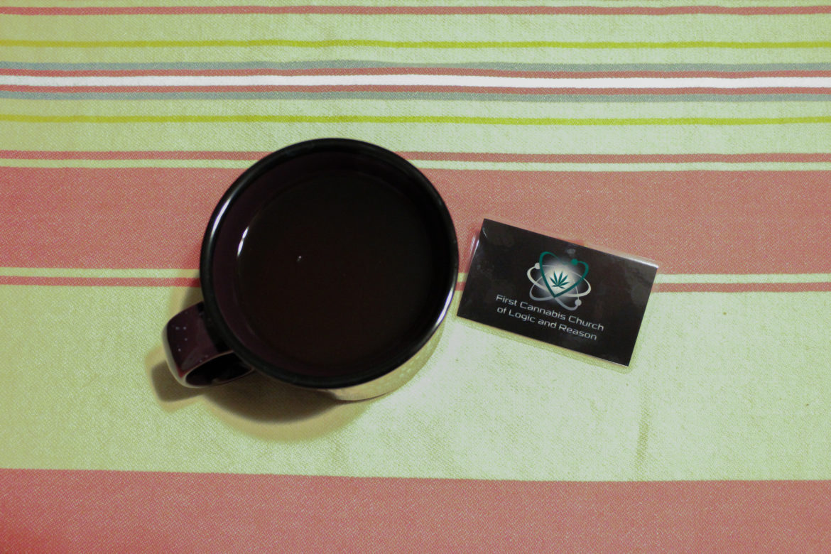 A portrait of a First Cannabis Church of Logic and Reason card next to a cup of coffee, part of the church's pay-it-forward campaign to fight stigma against marijuana users.