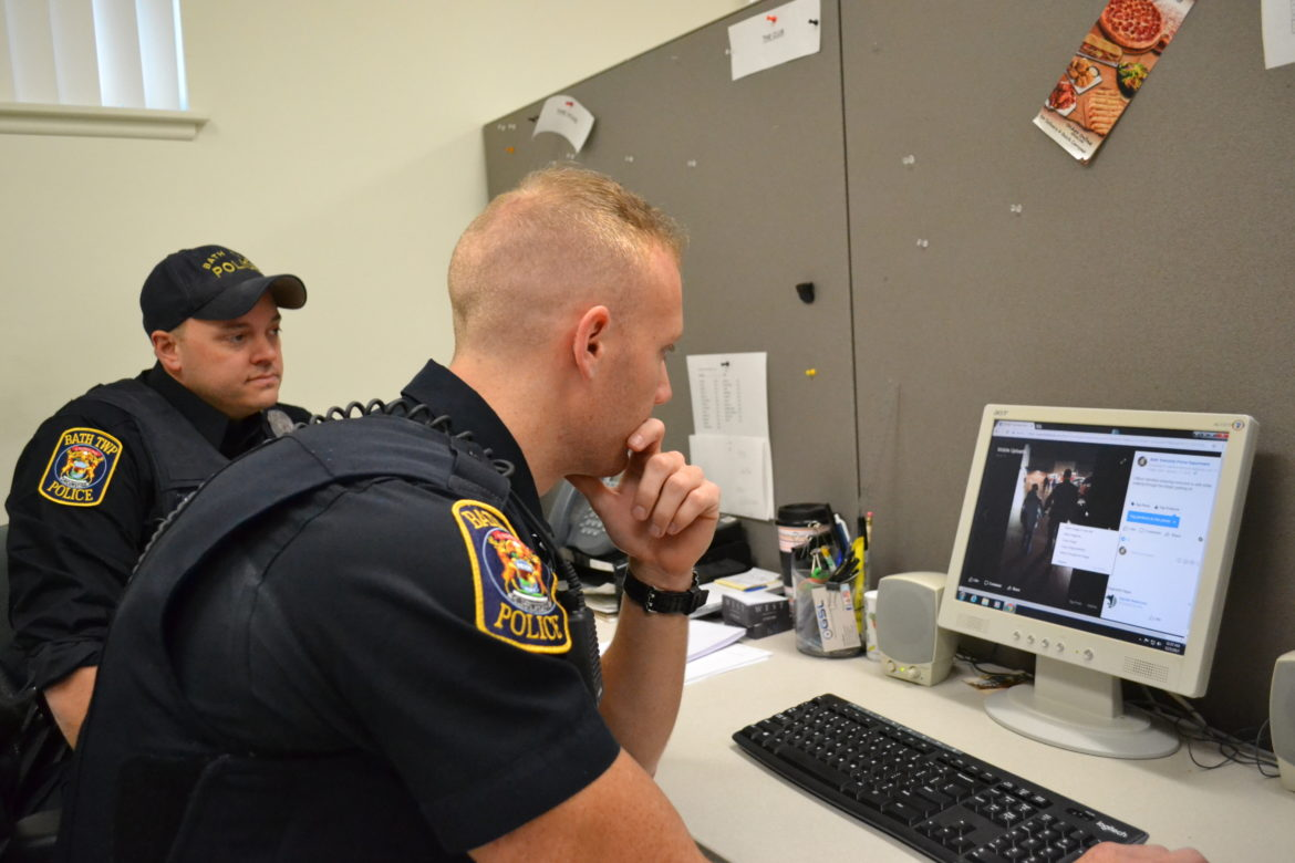 Officers Michael Lapham and Avery Lyon sit at the computer together