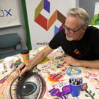 Karl Gude draws on a table covered in colorful sketches.