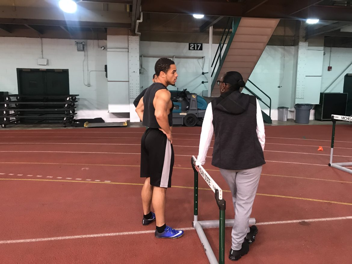 Coach Yolanda Johnson talking to a student-athlete about her hurdling form.