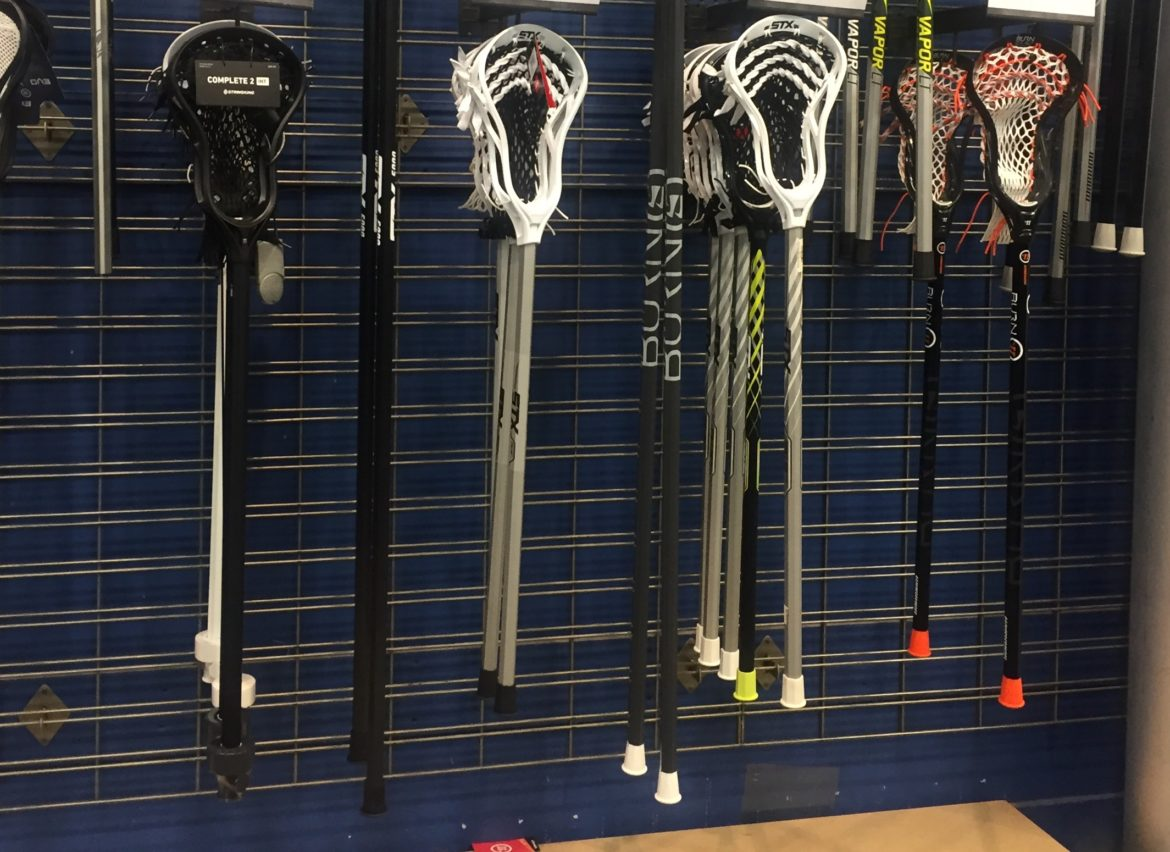 Lacrosse sticks hang on display in a sporting goods store.